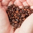 Stock Photo: Heart of coffee grains in hands
