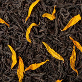 Black tea loose dried tea leaves and sunflower petals — Stock Photo