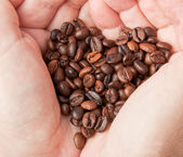 Heart of coffee grains in hands — Stock Photo