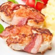 Grilled chicken patties wrapped strips of bacon and mashed potatoes - Stock Photo