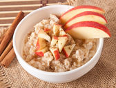 Oatmeal with apples and cinnamon in a white bowl — Stock Photo
