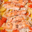 Pieces of salmon with potatoes, tomatoes and onions baked in the oven - Photo
