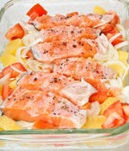 Pieces of salmon with potatoes, tomatoes and onions prepared for baking in the form — Stock Photo