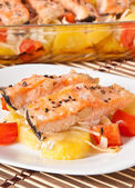 Pieces of salmon with potatoes, tomatoes and onions baked in the oven — Stock Photo