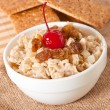 Oatmeal with raisins and cherries in a white bowl - Foto de Stock