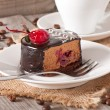 Sweet dessert fruitcake with a cherry and a cup of coffee — Stock Photo