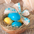 Easter eggs in nest on wooden background — Stock Photo