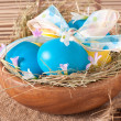 Royalty-Free Stock Photo: Easter eggs in nest on wooden background