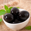 Royalty-Free Stock Photo: Black olives on a wooden table