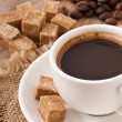 Closeup view of a cup of coffee, brown sugar and coffee beans - Stockfoto