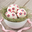 Easter eggs in a bowl decorated with a nest on the wooden table - Стоковая фотография