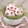 Stock Photo: Easter eggs in bowl decorated with nest on wooden table