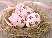 Easter eggs in nest on wooden table — Stock Photo
