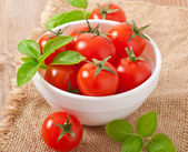 Cherry tomatoes in a bowl with basil — Stock Photo