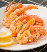 Fresh grilled shrimps with lemon on white plate — Stock Photo