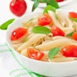Pasta salad with cherry tomatoes and fresh basil leaves — Stock Photo