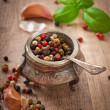 Mixture of pepper peas in an old bowl and basil leaves — Stock Photo