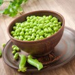 Green peas in a ceramic bowl on old wooden background — Stock fotografie