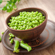 Green peas in a ceramic bowl on old wooden background — Stockfoto