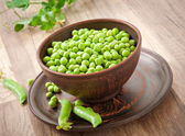 Green peas in a ceramic bowl on old wooden background — Stock Photo