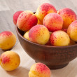 Bowl of fresh apricots on wooden table — Стоковая фотография