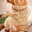 Wicker Christmas stocking filled with cookies, cinnamon sticks, candied lemon and star anise — Stock Photo