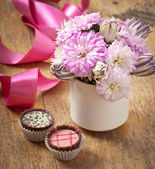 Beautiful aster flower bouquet and chocolates on wooden table — Stock Photo