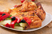 Small grilled chicken with vegetables on a white dish — Stock Photo