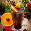 Christmas mulled wine in glass cup on a wooden table — Stock Photo