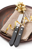 Close up of a knife and fork on ceramic plate with napkin on the white background — Stock Photo