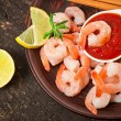 Tails of shrimps with fresh lemon and rosemary in a ceramic plate — Stock Photo
