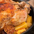 Baked whole chicken with potatoes, garlic and onion — Stock Photo