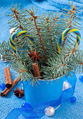 Christmas decorations and fir branches in the pail on the blue background — Stock Photo