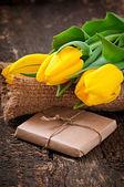 チョコレートの包装紙の木製の背景に黄色のチューリップの花束 — ストック写真