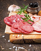 Assorted deli meats, rosemary and pepper — Stock Photo