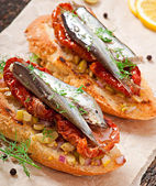 Crostini with anchovies, olives and sun-dried tomatoes — Stock Photo