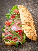 Sandwich with salami, lettuce — Stock Photo