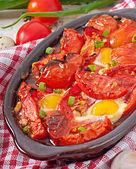 Baked tomatoes with garlic and eggs — Stock Photo