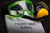 Health and safety register with goggles and earphones — Stockfoto