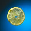 Slice of lemon on blue — Stock Photo #13131178