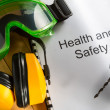 Health and safety Register with goggles, drill and earphones - Stock Photo