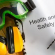 Stock Photo: Health and safety Register with goggles, drill and earphones