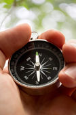 Hand holding silver black compass — Stock Photo