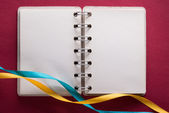 Open notebook with ribbons — Stock Photo