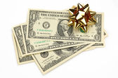 Dollars with decorative bow on white — Stock Photo