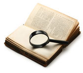 Magnifying glass and old book on the white background — Stock Photo