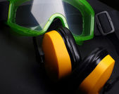 Green goggles with earphones on black — Stock Photo