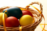 Easter eggs with yellow ribbon in basket — Stock Photo