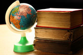 Pile of old books, globe — Stock Photo