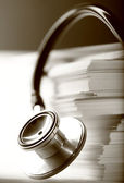 Stethoscope and heap of paper cards — Stock Photo